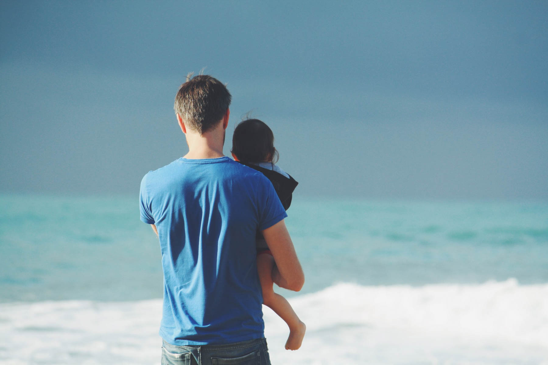 Father with child at ocean